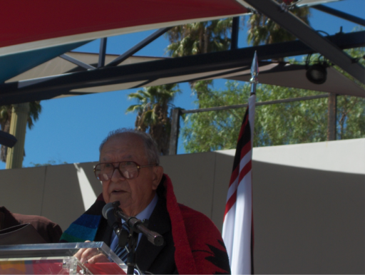 Man in brightly-colored shawl speaking at podium in front of Gabrielino/Tongva flag