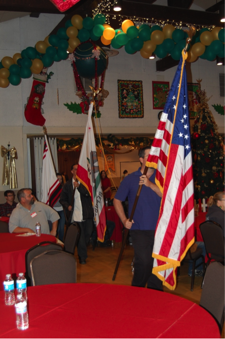 U.S., California and Gabrielino/Tongva flags being led in procession in banquet room decorated for Christmas