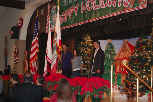 U.S., California and Gabrielino/Tongva displayed on stage decorated for Christmas