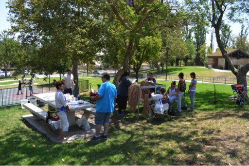 People gathered around picnic tables in park