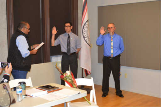 Men in shirts and ties in office raising their right hands as another man reads oath