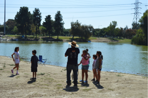 Alt-text: Man demonstrating fishing pole to children on shore of lake in park