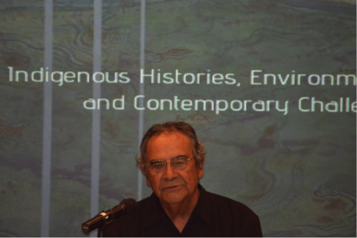 "Man speaking into microphone in front of slide reading (in part) ""Indigenous Histories"""