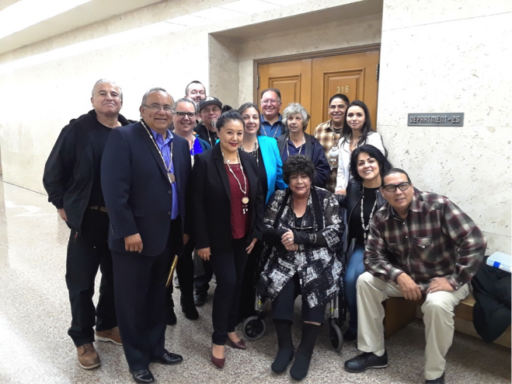 Group of more than a dozen men and women in modern attire with traditional necklaces posing outside of door to courtroom
