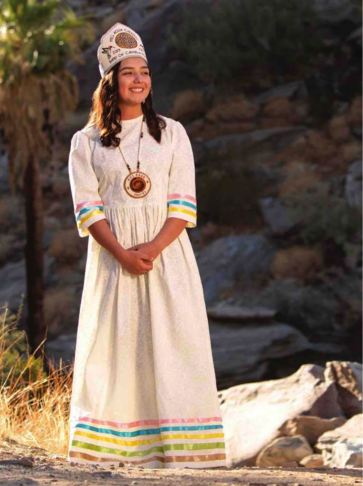 Photo of smiling young woman in cream-colored costume with embroidered conical hat, beadwork pendant and pastel-colored stripes on the lower sleeves and skirt, posing in desert landscape with rocks and palm trees