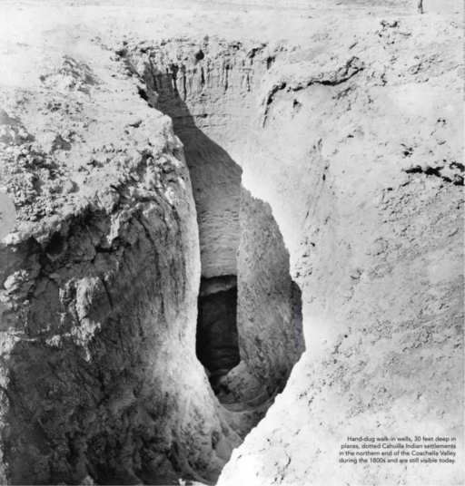 Black-and-white photograph of opening in ground with rough-hewn staircase winding down into a cavern