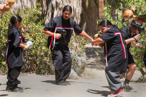 Photo of young men in black shirts with red and white ribbon decorations shaking gourd rattles and dancing in a grove of palm trees