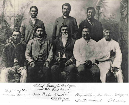 Old photograph of eight men posed sitting and standing in formal 19th-century attire, centered around the white-bearded chief holding a walking stick