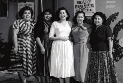 "Black-and-white photo of five women in elegant 1950s dresses standing in front of a building with signs reading ""Bureau of Indian Affairs, Ned Mitchell, Agent"" and (partly obscured) Tribal Council 1965"
