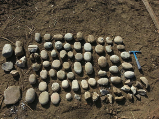 A collection of stone tools, mostly round-edged, flat stones, laid out in dirt beside an archaeologist's hammer