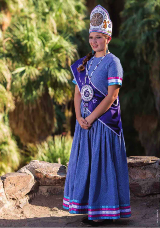 Photo of smiling young woman in purple costume with embroidered conical hat, sash, beadwork pendant and shimmering stripes on the lower sleeves and skirt, posing in desert landscape with rocks and palm trees