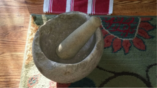 Ancient stone mortar and pestle displayed on colorful modern mat