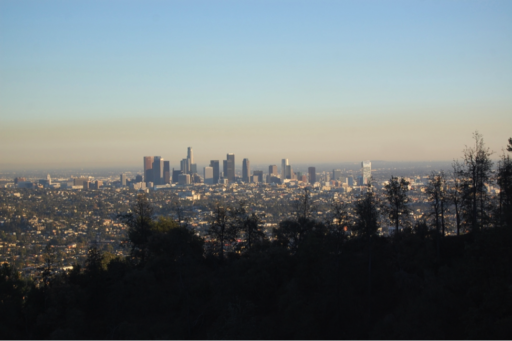 Silhouette of mountain and treeline with city skyline in background under a hazy sky