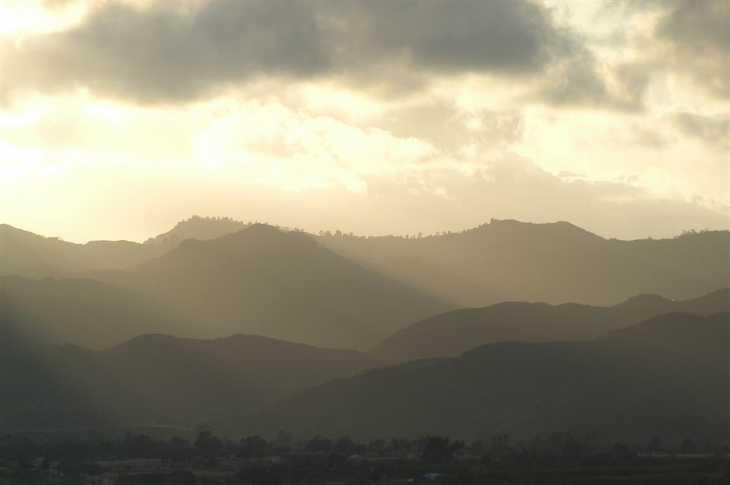 Golden sunlight and clouds above a mountain range in silhouette