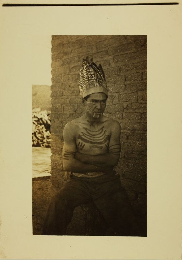Sepia-toned photograph of a man with crossed arms in feathered headdress and body decorations