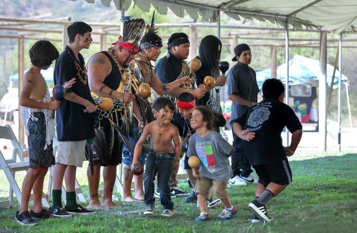 Young men and boys dancing and shaking gourd rattles in a mix of traditional regalia and modern dress