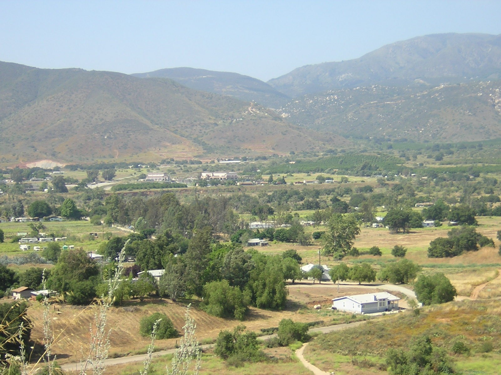 A lightly wooded valley surrounded by desert mountains with houses, roads, and agricultural fields