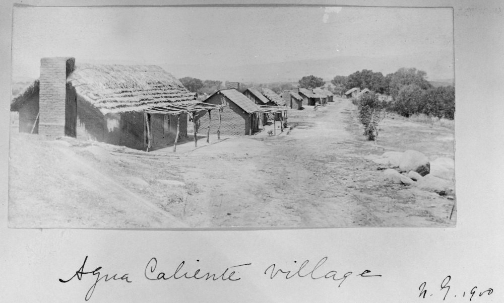 Old photograph of a neat row of houses with adobe walls and thatched roofs along a dirt road