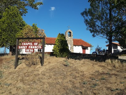 Color photograph of 19th-century adobe chapel with stone belfry and red tile roof