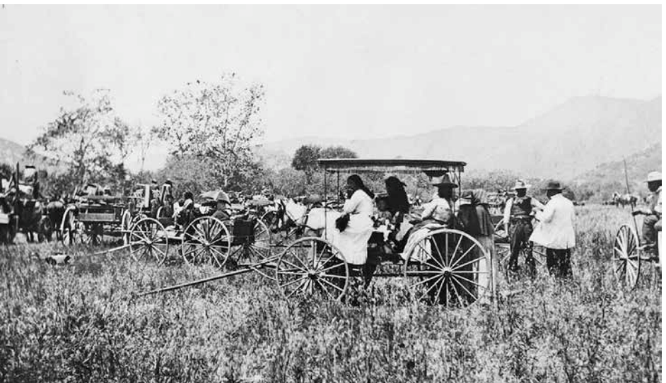 Old photograph of families waiting in and around unhitched wagons in an overgrown field with mountains in background
