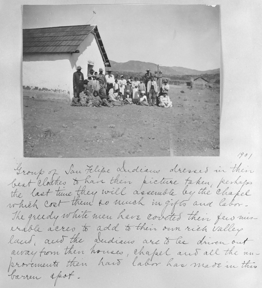 "Old photograph of men, women and children sitting and standing in front of an adobe building with handwritten text that reads: ""1901: Group of San Felipe Indians dressed in their best clothes to have their picture taken, perhaps the last time they will assemble by the chapel which cost them so much in gifts and labor. The greedy white men have coveted their few miserable acres to add to heir own rich valley land, and the Indians are to be driven out away from their houses, chapel and all the improvements their hard labor has made in this barren spot."""