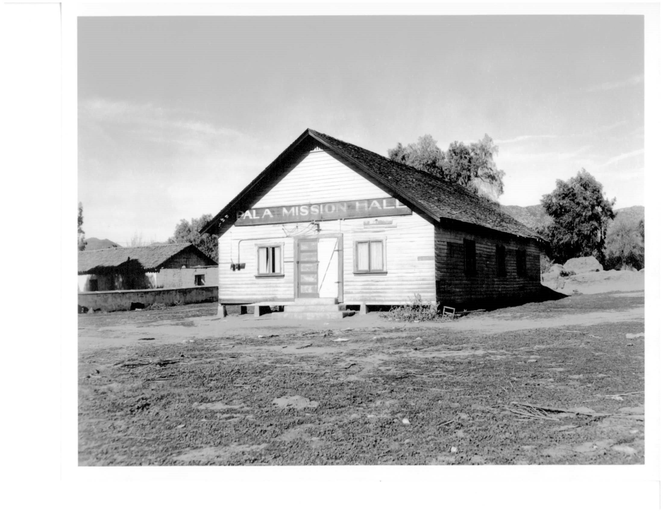 "Old photograph of wooden building on piles with sign reading ""Pala Mission Hall"""
