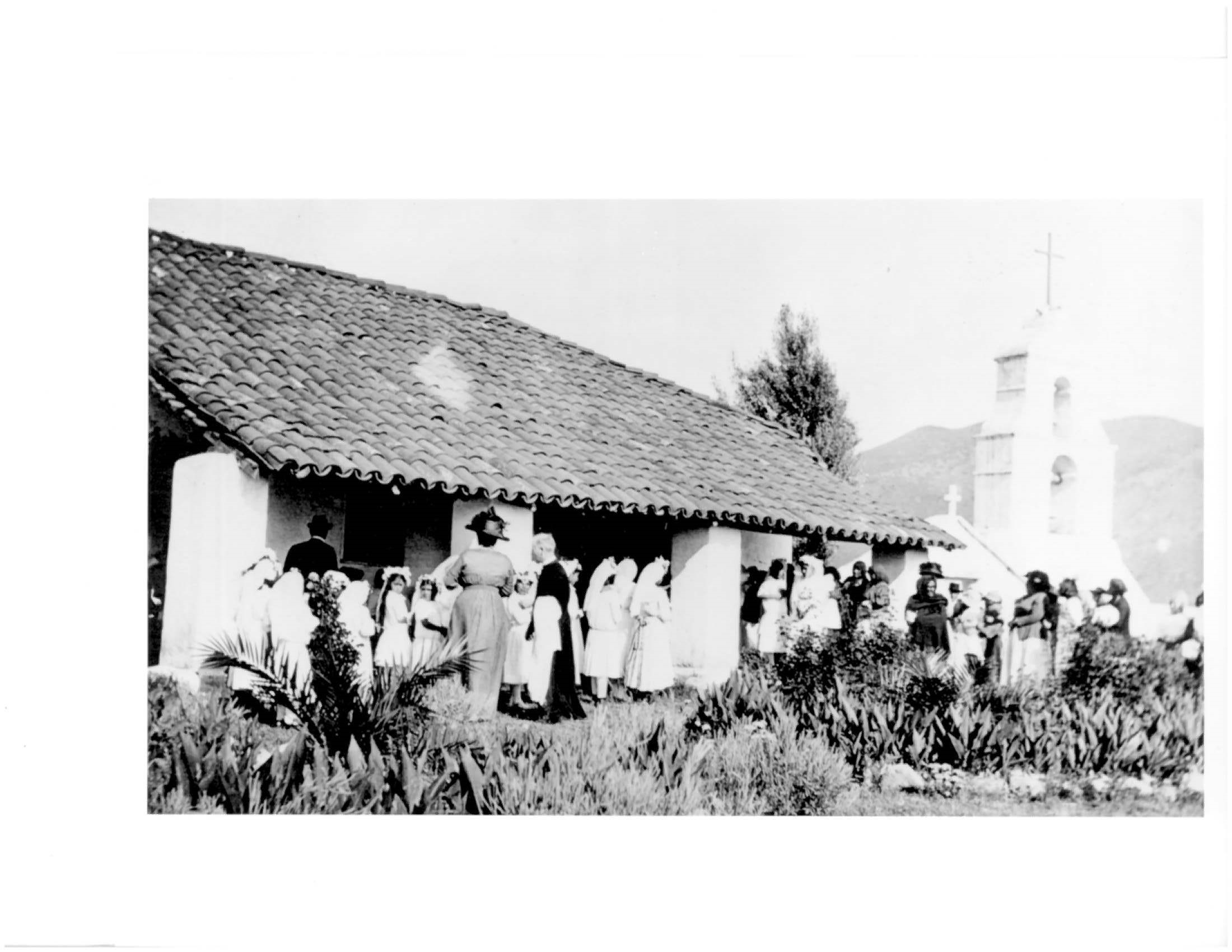 Old photograph of people in white dresses and other finery in front of tile-roofed adobe surrounded by agave plants with belfry in background