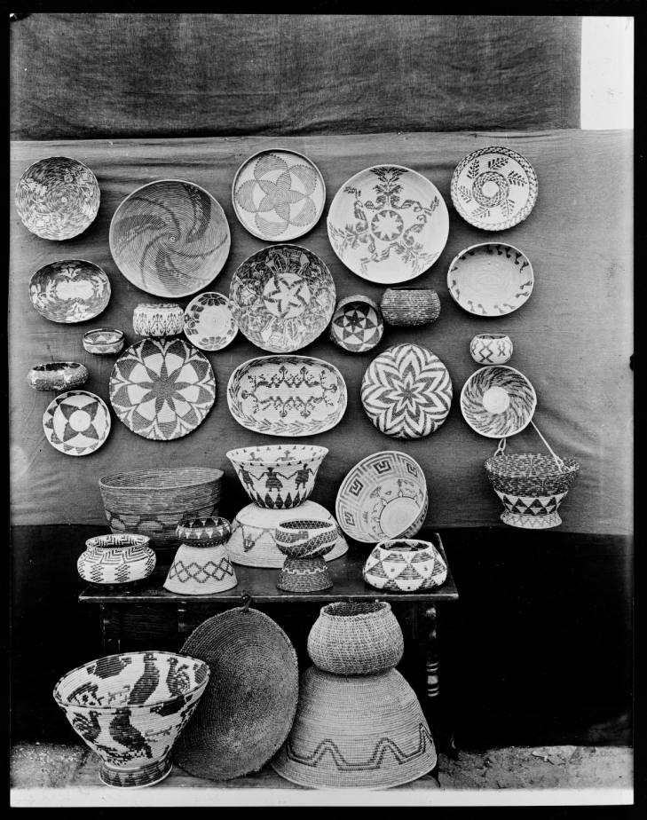 Black-and-white photograph of a collection on baskets with abstract and representational designs including stars, frets, spirals, birds, human figures and foliage patterns