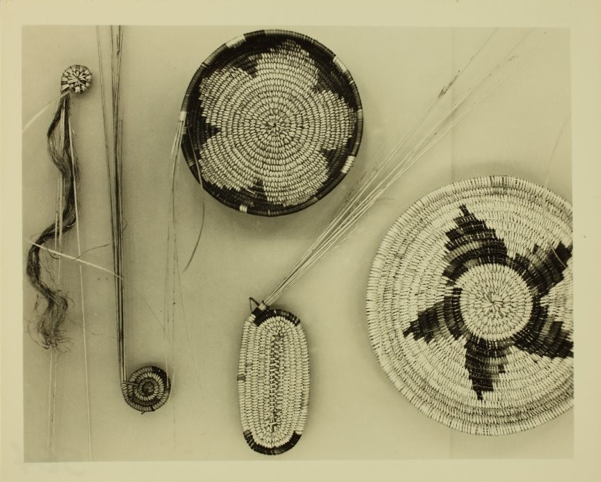 Sepia-toned photograph of coiled basketry at different stages of development from raw materials to finished product