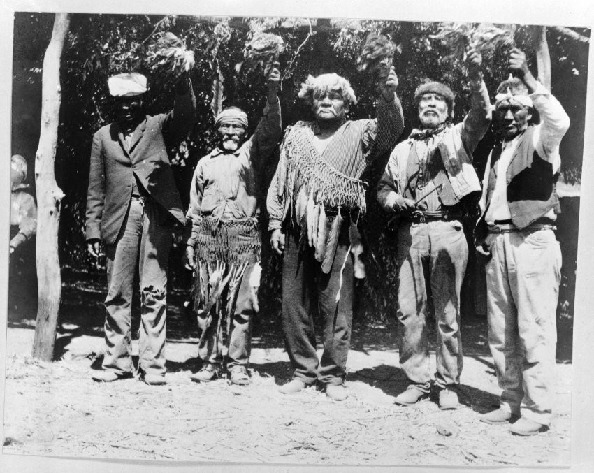 Old photograph of men wearing a mix of Western clothing and traditional regalia including headdresses and feathered sashes hold up rattles decorated with feathers