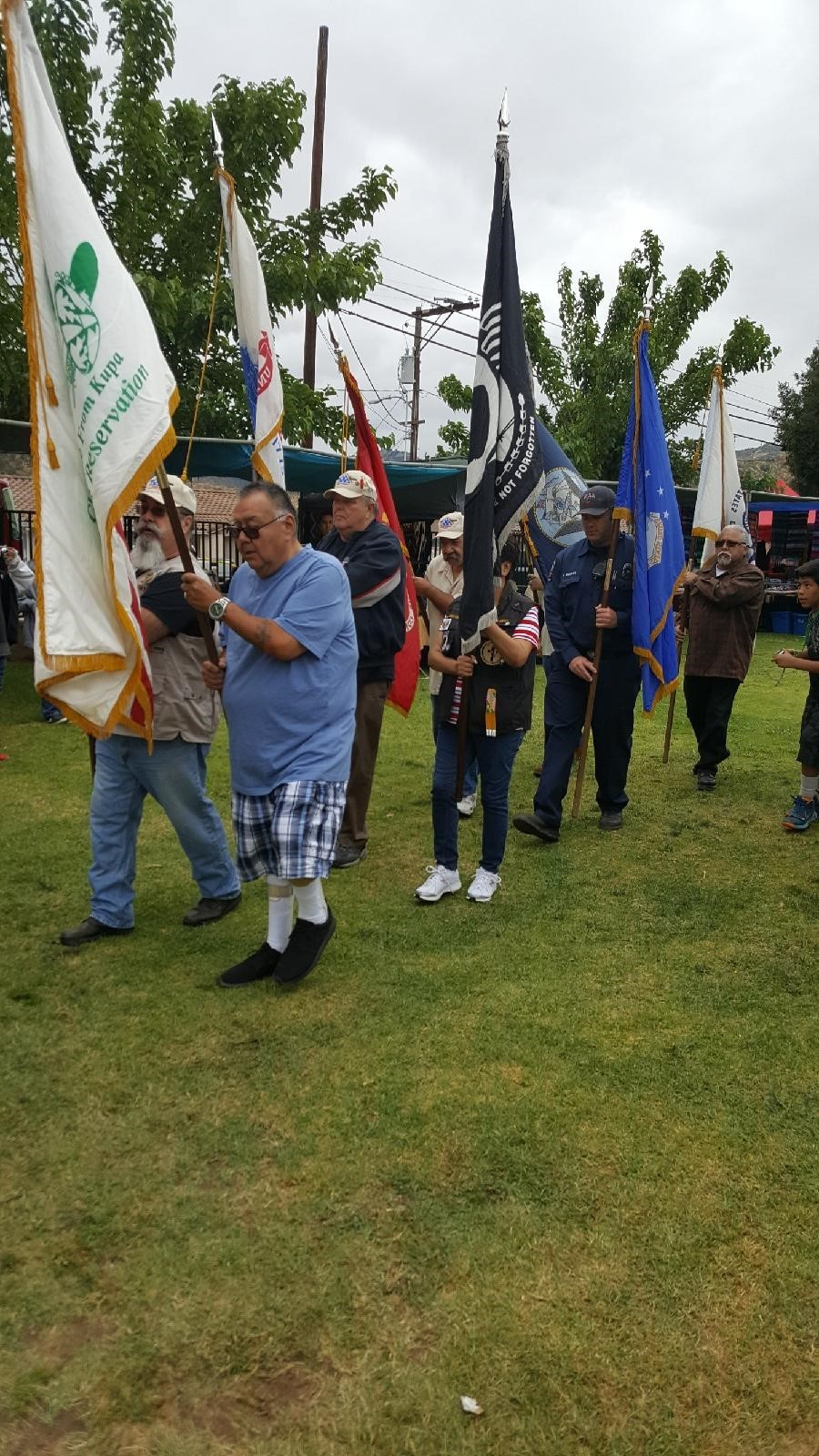 A procession of men in modern dress holding tribal and POW-MIA flags