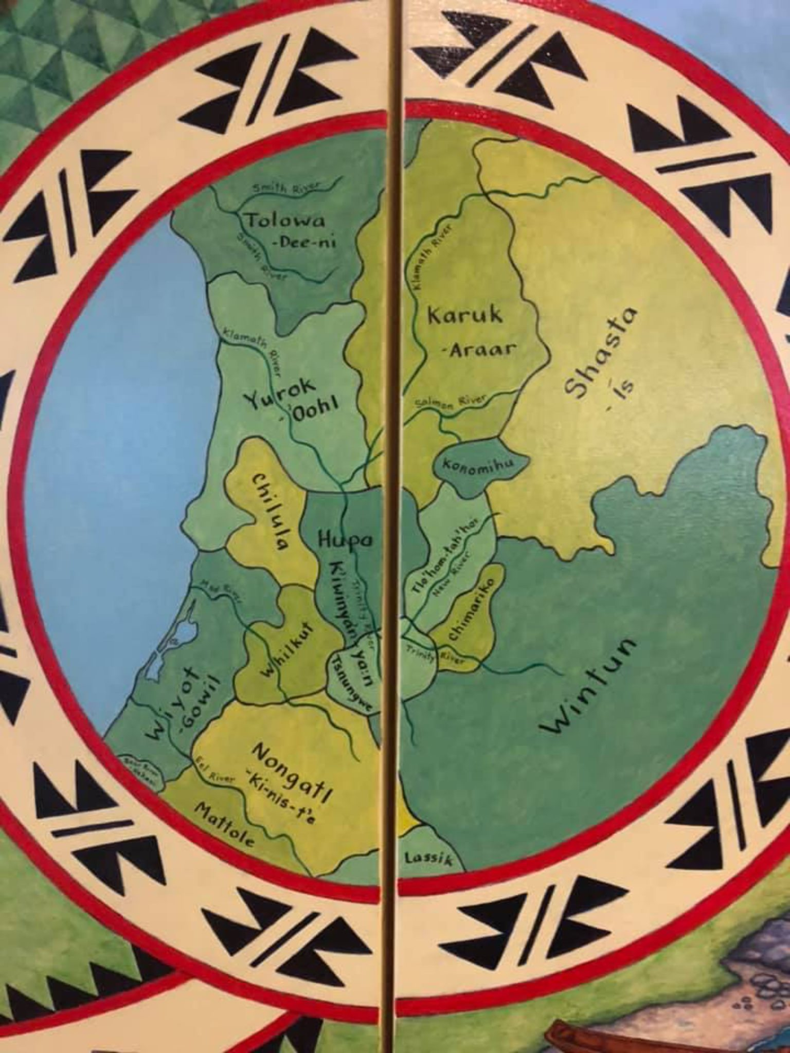Hand-painted map of parts of Humboldt, Siskiyou, Trinity and Del Norte counties on two panels showing indigenous cultural areas in shades of green, with a traditional pattern in red, beige and black encircling it