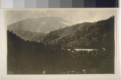 Sepia-toned photograph of a wooded valley with the silhouette of a flat-topped mountain in the background