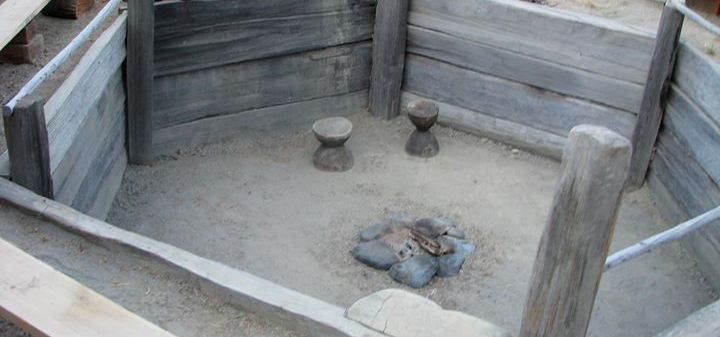 A submerged octagonal space with wooden plank walls and a dirt floor with a stone firepit and stools